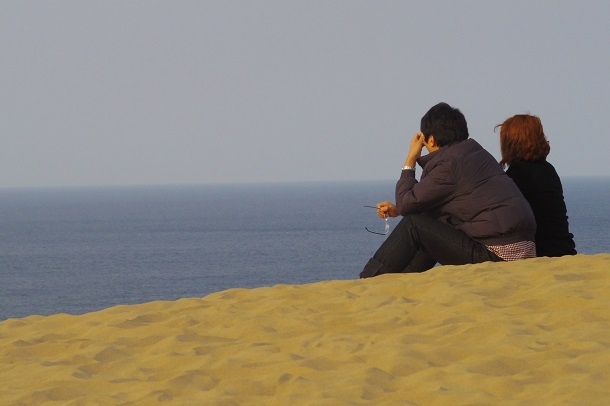 砂丘で黄昏るカップルの写真