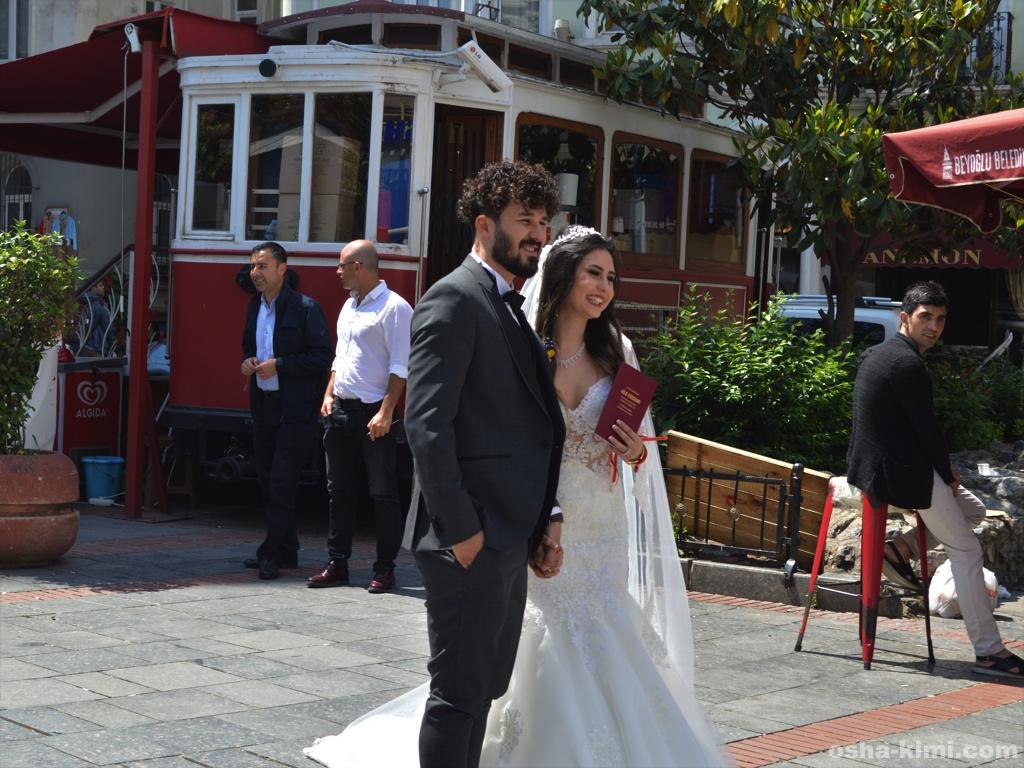 ガラタ塔の下でウェディングフォトを撮っている新婚カップル